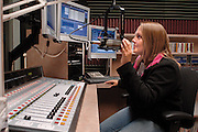 Lauren Bindley, a broadcast journalism major and morning host, demonstrates the use of WOUB-AM's new equipment, which includes a Wheatstone digtial broadcast console, a Netia digital audio workstation and flat-screen monitors.The equipment was purchased with a grant comprised of federal and state funds. The grant also enabled all five studios to be linked to the same server, allowing students to access digital files regardless of location. ..Photo by Neil Osborne