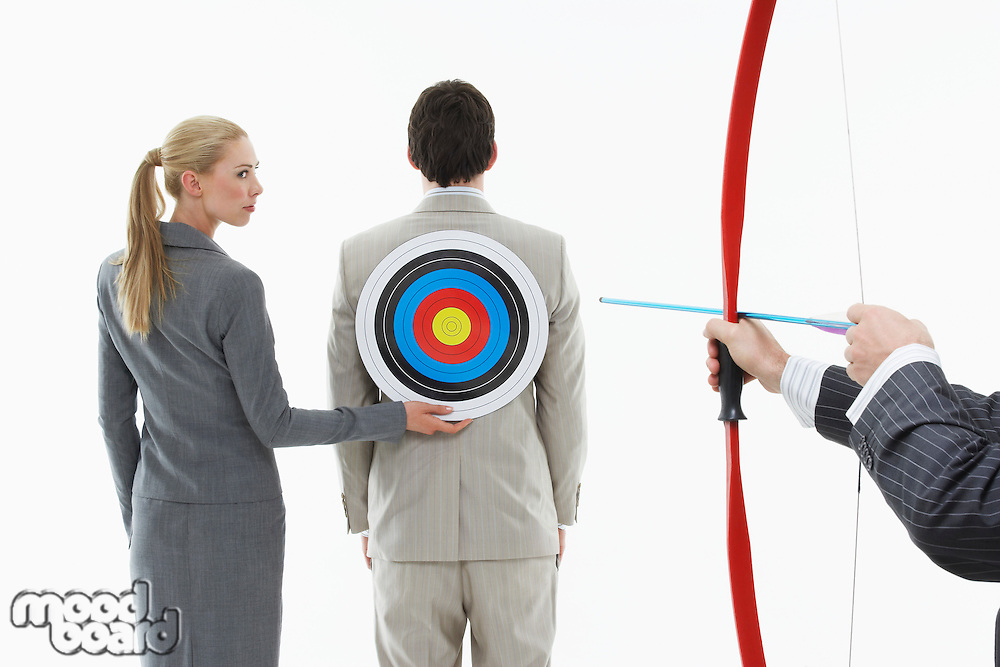 Business woman holding target to man's back while other man (close-up of hands) aims bow and arrow against white background