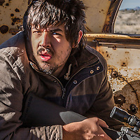 Crazy Louis.  Model/photographer Louis Curson-Mayorga poses in an old shot up school bus found just off of Mojave Road, located in the Mojave National Preserve, CA.