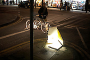 A cyclist pushes his bike across a road junction near a crushed traffic bollard in London's Tottenham Court Road.