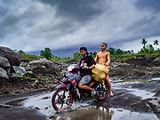 29 JANUARY 2018 - GUINOBATAN, ALBAY, PHILIPPINES: Boys bringing coconuts off the volcano cross a river in the lava bed of Mayon volcano. The volcano's eruptions have loosened rock and gravel on the mountain, increasing the chances for rockslides and floods to communities near rivers coming down the mountain. Mayon volcano's eruptions continued Monday. At last count, more 80,000 people have been evacuated from their homes of the slopes of the volcano and are crowded into shelters in communities outside of the danger zone.    PHOTO BY JACK KURTZ