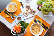 Overhead shot of breakfast table with fruit, corn flakes, toasted bread with chocolate cream and coffee, with orange tablecloths.
