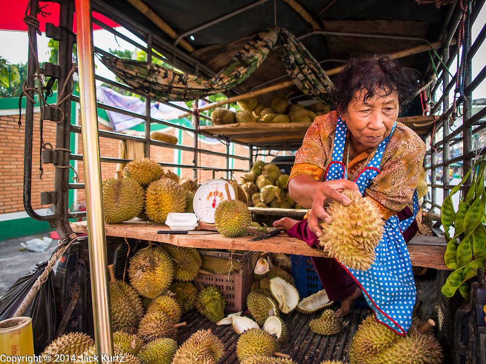 27 JULY 2014 - HAT YAI, SONGKHLA, THAILAND:   A woman sells durian from the back of a pickup truck in Hat Yai. Hat Yai is the 4th largest city in Thailand and the largest outside of the Bangkok metropolitan area. It's less the 50 miles from the Malaysian border and is a popular vacation spot for Malaysian and Singaporean tourists.     PHOTO BY JACK KURTZ