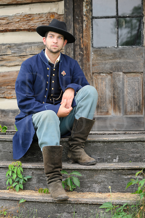 Soldier sitting on log cabin house steps, American Civil War Union infantry private reenactor portrayal.