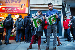 © Licensed to London News Pictures. 16/01/2015. LONDON, UK. A couple reading copies of Charlie Hebdo's survival edition after buying it from 'La Page' book shop in London on Friday, 16 January 2015. Photo credit : Tolga Akmen/LNP
