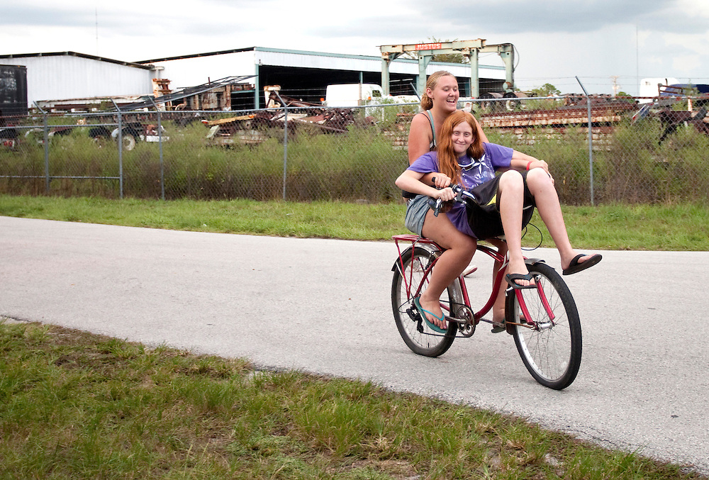 Two girls share a smile and bicycle on the roads of Bithlo.  <br /> [WILLIE J. ALLEN JR.]