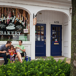 A family sitting outside the Sassafras Bakery during the farmer's market in Worthington on High Street Saturday June 21, 2014. (Christina Paolucci, photographer).