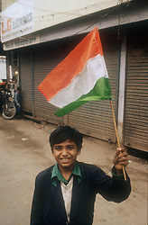 Boy waving the Indian flag and smiling,