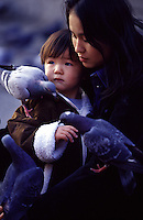 A mother reassures her young son feeding the pigeons at Sensoji Temple, Asakusa, Tokyo, Japan
