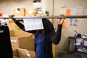 Foster child Aleta moves a clothing rack in the stock room at Goodwill in Milpitas, California, on September 26, 2013. (Stan Olszewski/SOSKIphoto)