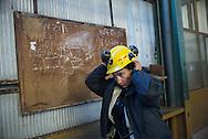 Valetina Zurru mentre si aggiusta i lunghi capelli neri sotto il caschetto prima di entrare in miniera