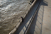 An aerial view of a man looking into the waters of the the Thames river from Fishmongers Hall Wharf in the City of London, on 10th October 2018, in London, England.