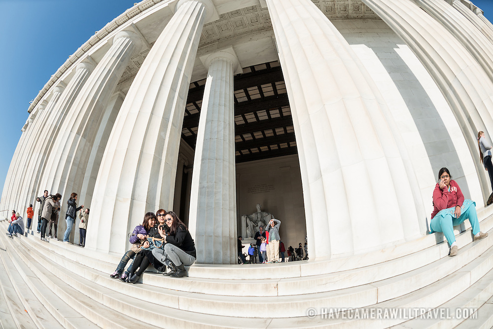 Tourists sit on the steps of the Lincoln Memorial in the sun in Washington DC.