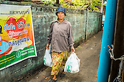 "11 JANUARY 2013 - BANGKOK, THAILAND:    A woman walks home with her shopping in the Ban Krua neighborhood in Bangkok. The Ban Krua neighborhood of Bangkok is the oldest Muslim community in Bangkok. Ban Krua was originally settled by Cham Muslims from Cambodia and Vietnam who fought on the side of the Thai King Rama I. They were given a royal grant of land east of what was then the Thai capitol at the end of the 18th century in return for their military service. The Cham Muslims were originally weavers and what is known as ""Thai Silk"" was developed by the people in Ban Krua. Several families in the neighborhood still weave in their homes.                PHOTO BY JACK KURTZ"