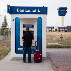 Father Adday, 34, withdraws money at an ATM at the airport in Nevsehir, a city in central Turkey. He has come to the area to visit Iraqi Christian refugees.