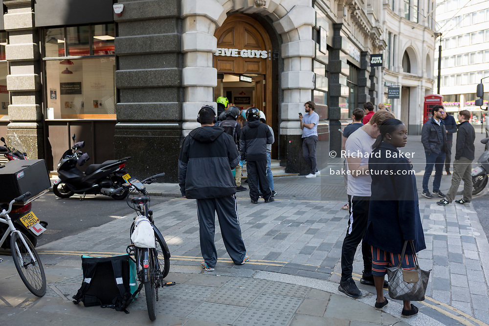 As the UK's Coronavirus death toll during the government's social distancing lockdown, rose by 384 to 33,998, and the R rate of infection is reported to be between 0.7 and 1.0, customers and Uber Eats riders wait for their orders outside a Five Guys restaurant who are open only for take-aways and deliveries, in accordance with government lockdown guidelines, on 15th May 2020, in London, England.