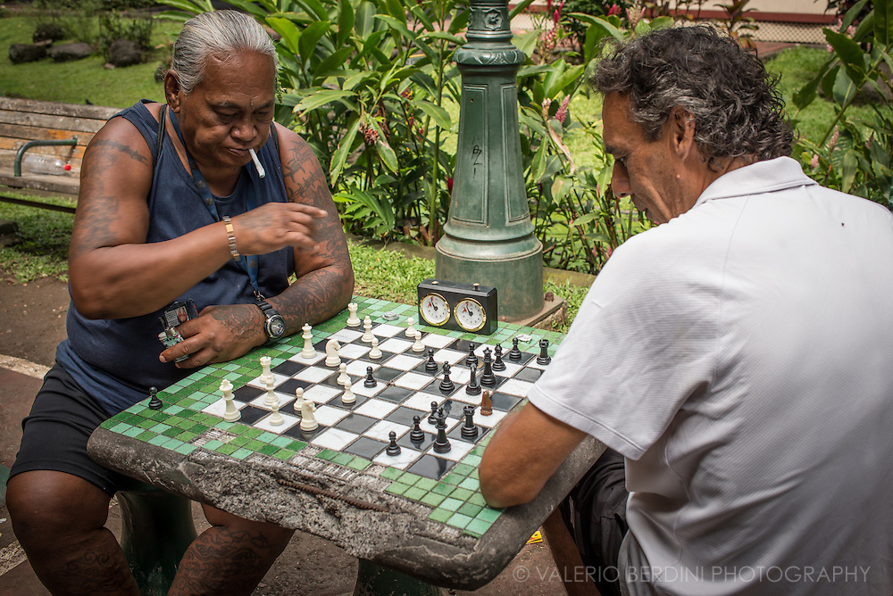 two men play a game of chess on a marble table in the Bougainvillea Park a public garden in Papeete.