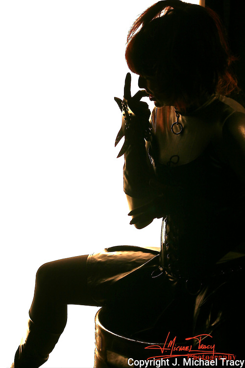Silhouette of a fetish model sitting on a drum in front of a white backdrop.