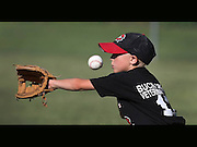 Bryce Gorman faces an incoming throw during youth baseball action at Sunset Park in Knightstown.