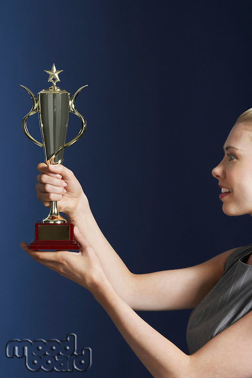 Woman holding and admiring trophy against dark background profile
