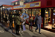 Young women carry 24th birthday party balloons while waiting for the next service at a bus stop on Westminster Bridge, on 15th November 2018, in London, England.