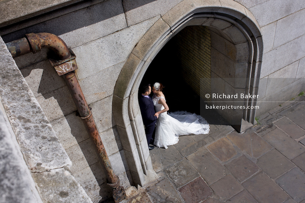 Chinese wedding couple have their formal portrait taken in a tunnel opposite the Palace of Westminster, London.