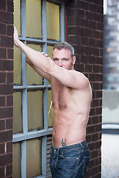 shirtless man on a rooftop in New York City taking off his pants