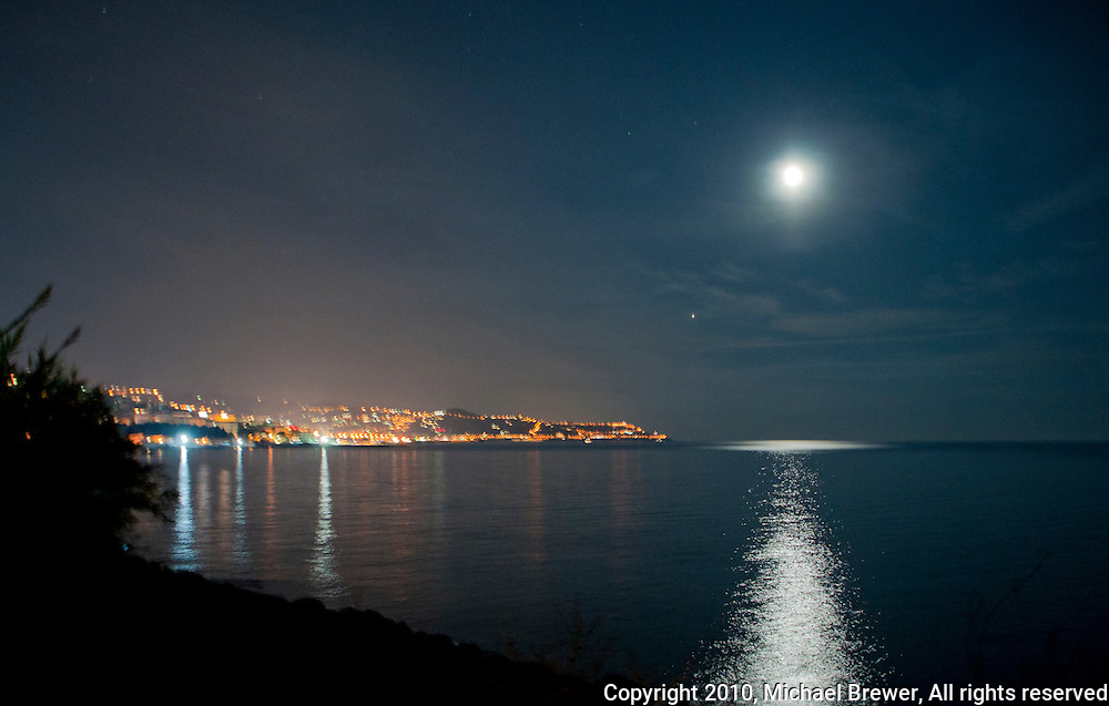 The full moon shining over a calm sea at San Remo, Italy.