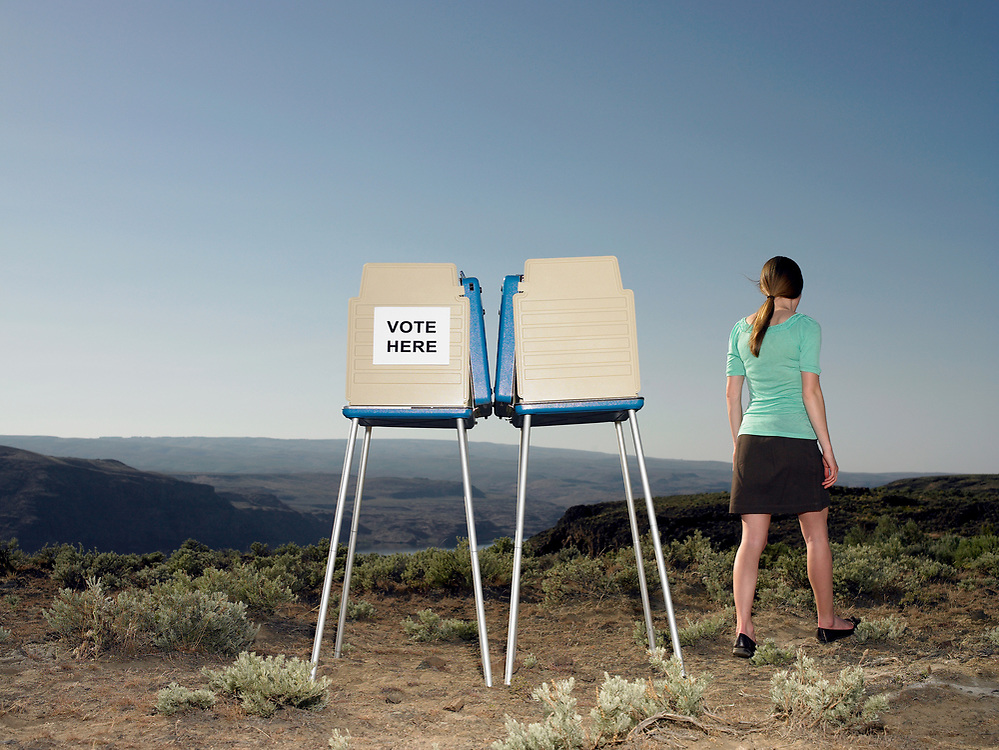 Young woman walking away from outdoor voting booth.