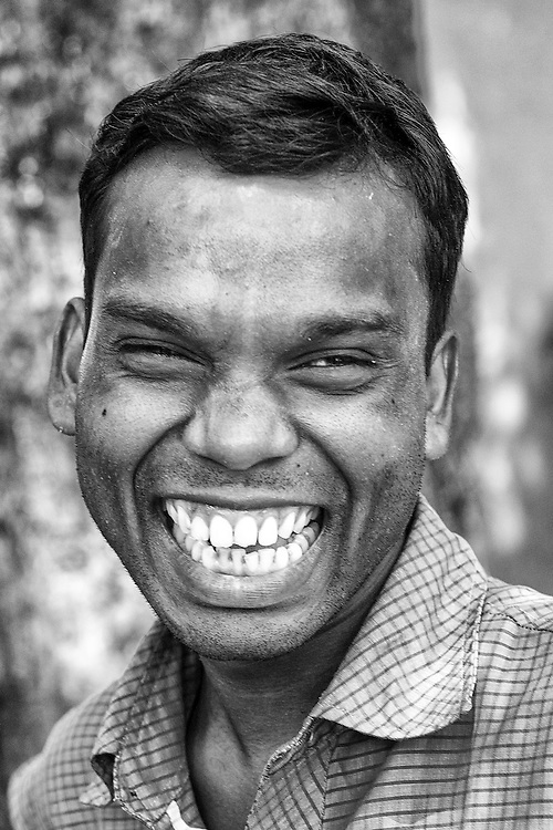 Black and white portrait of a middle age adult smiling widely at the camera