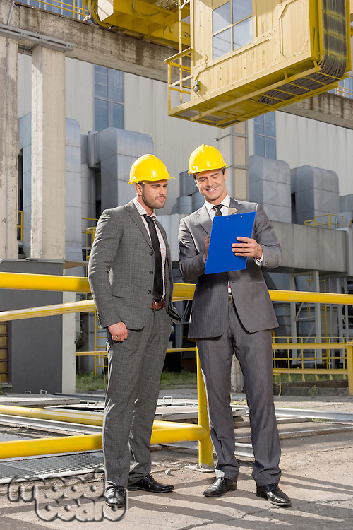 Full length of young businessmen with clipboard discussing at construction site