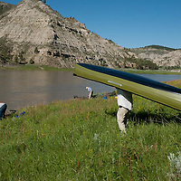 man packs pakboat canoe to the shore of the missouri river in the umrbnm, montana
