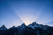 """Crepuscular rays,"" or ""God Beams"" erupting as the sun sets behind the Grand Teton and Teewinot Mountain in Grant Teton National Park near Jackson Hole, Wyoming"