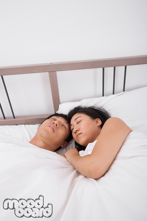 Asian couple sleeping in bed