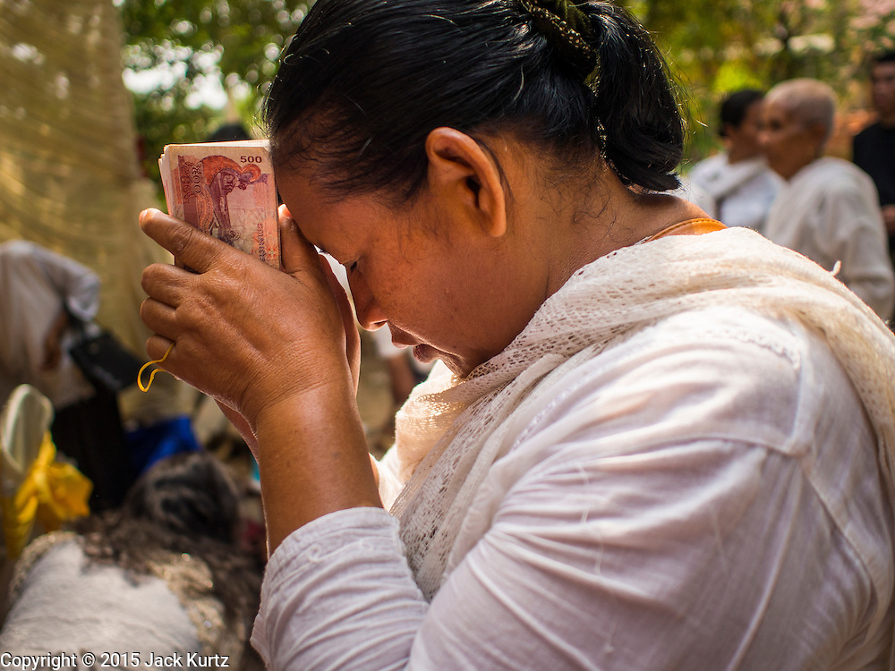 15 MARCH 2015 - SIEM REAP, SIEM REAP, CAMBODIA: A woman prays with cash she is donating to monks at the annual mass merit making at Wat Bo in Siem Reap. More than 1,200 Buddhist monks, from across Siem Reap province, received alms from Buddhist lay people during the morning long ceremony. Wat Bo was originally built to be a the temple for Siamese (Thai) troops when Siem Reap and western Cambodia were controlled by Siam (Thailand). Now Wat Bo is one of the most important temples in Siem Reap.      PHOTO BY JACK KURTZ