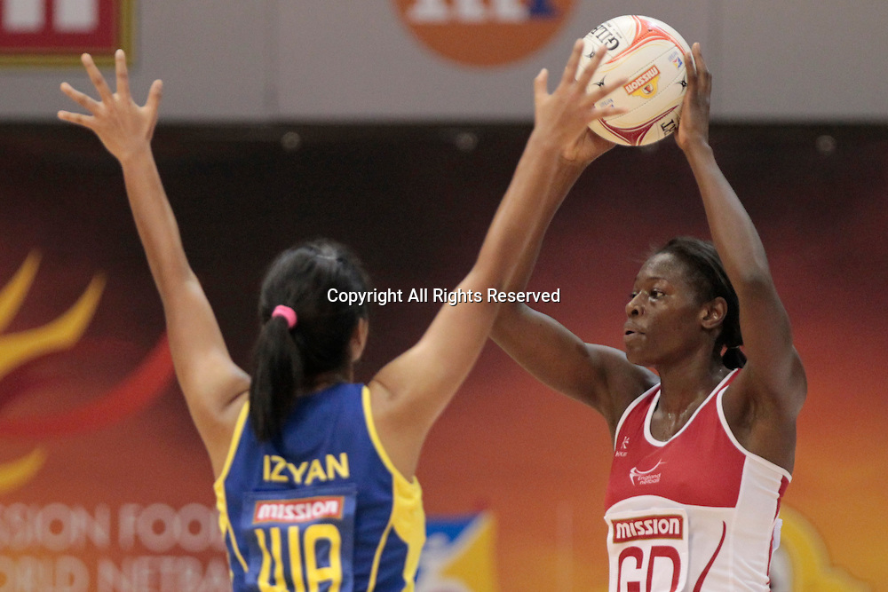 06.07.2011 Izyan Syazana of Malaysia(left) attempts to block Sonia Mkoloma during the Pool D match between England VS Malaysia, Mission Foods World Netball Championships 2011 from the Singapore Indoor Stadium in Singapore.