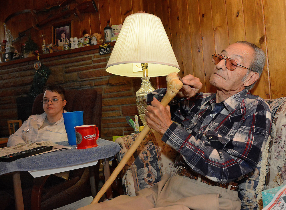 jt120916p/biz/jim thompson/  Henry Gallegos works on one of his walking sticks that he makes as they watch some TV.  Friday Dec. 09, 2016. (Jim Thompson/Albuquerque Journal)