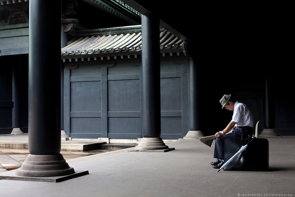 Man reading a newspaper inside a Chinese style black temple in Ochanomizu, Tokyo
