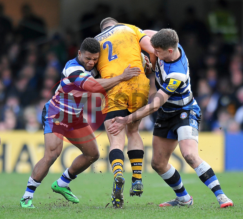 Kyle Eastmond and Ollie Devoto (Bath) put in a double-tackle on Tom Lindsay (Wasps) - Photo mandatory by-line: Patrick Khachfe/JMP - Tel: Mobile: 07966 386802 22/02/2014 - SPORT - RUGBY UNION - The Recreation Ground, Bath - Bath v London Wasps - Aviva Premiership.