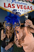 Two women celebrating in front of Welcome to Las Vegas sign