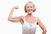 Portrait of senior woman flexing muscles against white background