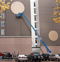 Men working - installing a decorative circle on the wall of a building in Seattle, Washington, USA