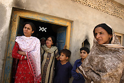 Left to right, Safia Firdos and Razia Samad, female members of the local police department, near the end of their eight-day security shift to protect Mukhtar Mai, far right, Meerwala, Pakistan, April 27, 2005. Mai, 33, went against the Pakistani tradition of committing suicide when she brought charges against the men who gang raped her nearly three years ago. Mai, says she feels secure currently but is not sure how long she will need to have such intense protection. A police station is being built across the street from her home.