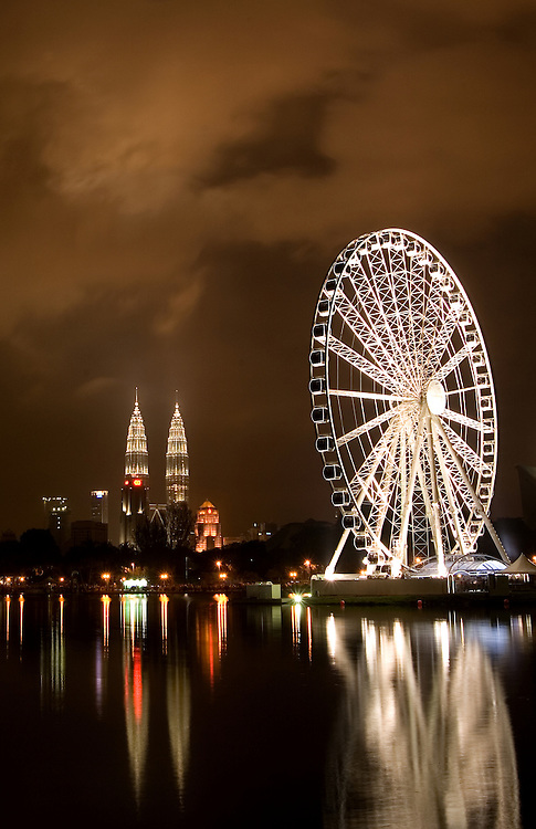 A 60-metre-high Ferris wheel stands against Petronas Towers at night in Kuala Lumpur, Malaysia.