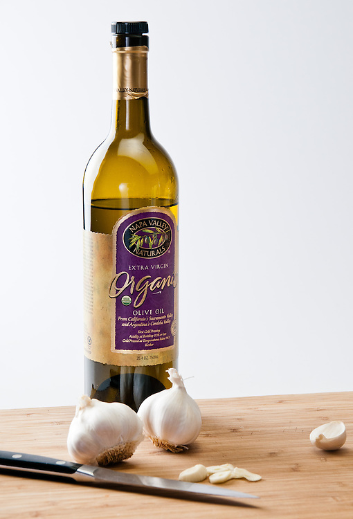 garlic and olive oil on a cutting board with a knife