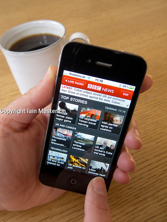 Reading BBC News online with an Apple iphone 4G smart phone