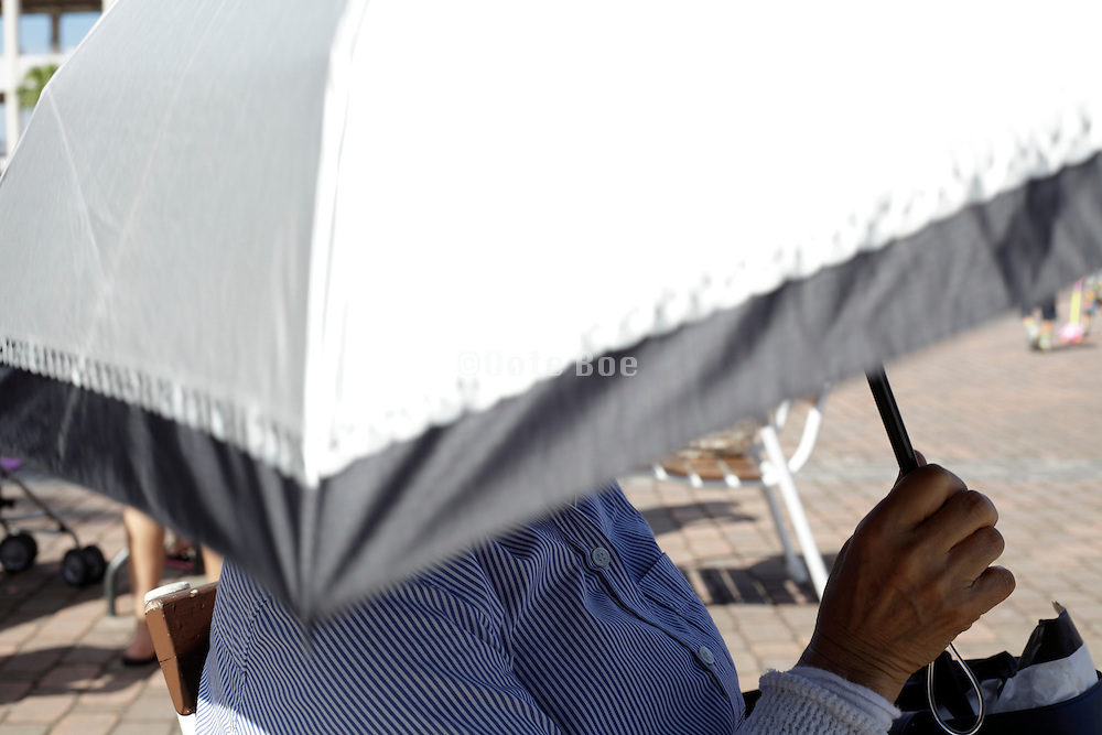 female person holding an umbrella for protection against the sun