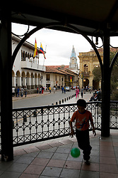 Boy playing with soccer ball in gazebo, Cuenca, Ecuador, South America.  Cuenca is a UNESCO World Heritage Site.