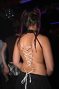young female model with 12 ring piercings on her back in the shape of a corset with a ribbon tied through them