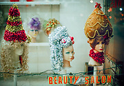 Beauty salon mannequin heads with holiday wigs decorated like Christmas trees